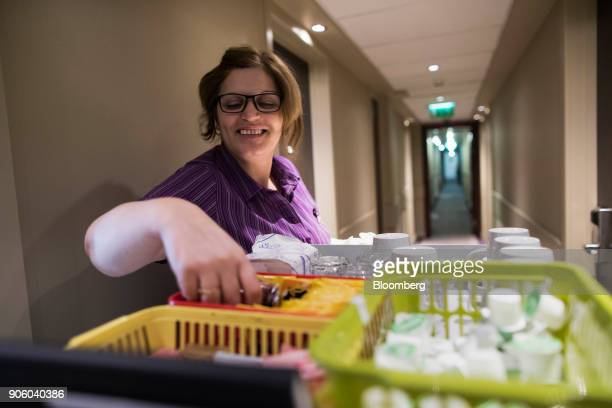 A chambermaid restocks a bedroom with teabags from a trolley at a Premier Inn hotel operated by Whitbread Plc in London UK on Wednesday Jan 17 2018...