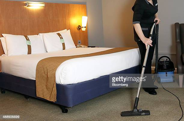 A chambermaid vacuums the floor of a guest room in this arranged photograph taken inside a Holiday Inn hotel operated by InterContinental Hotels...