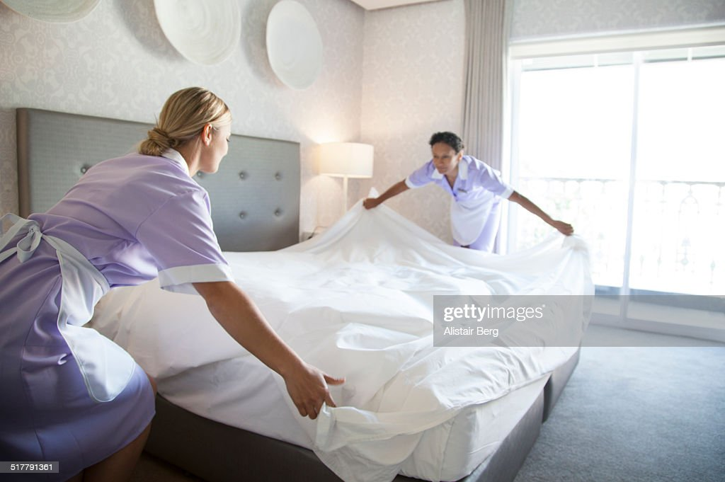 Chambermaids making bed in hotel room : Stock Photo