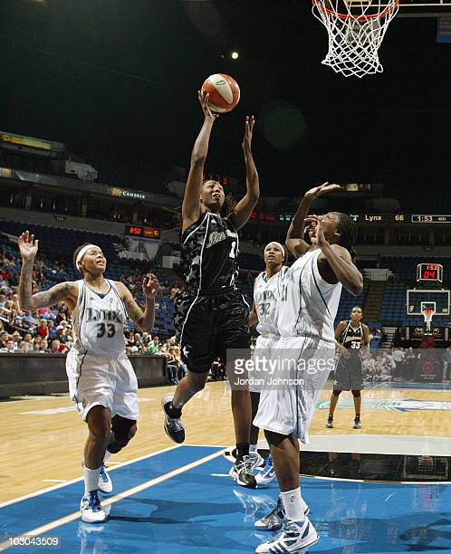 Chamique Holdsclaw of the San Antonio Silver Stars puts up a shot against Nicky Anosike and Seimone Augustus of the Minnesota Lynx during the game on...