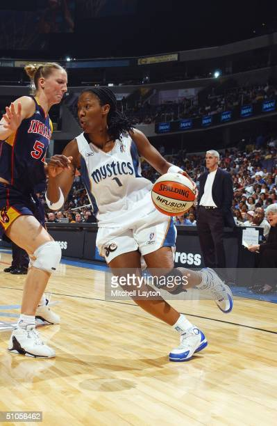 Chamique Holdsclaw of the Washington Mystics drives around Kristen Rasmussen of the Indiana Fever during the game at the MCI Center on July 1 2004 in...