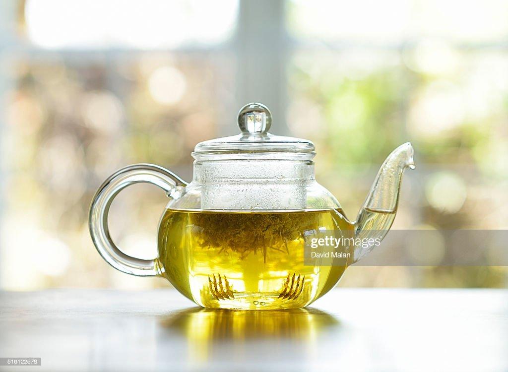 Chamomile tea in a clear teapot : Stock Photo