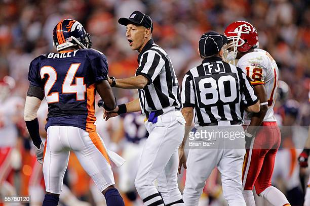 Champ Bailey of the Denver Broncos gets held back by back judge Tony Steratore while field judge Greg Gautreaux restrains wide receiver Samie Parker...