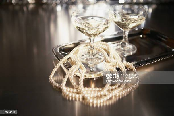 Champagne and pearl necklace on tray