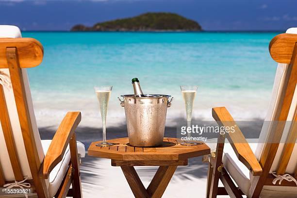 champagne et des chaises longues sur une plage tropicale dans les Antilles