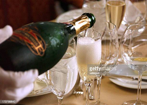 Champagne being poured in a tall glass for an elegant dinner