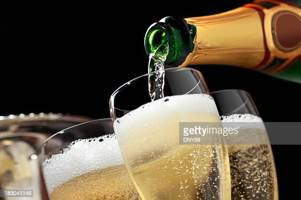 champagne being poured into champagne glasses - fles stockfoto's en -beelden