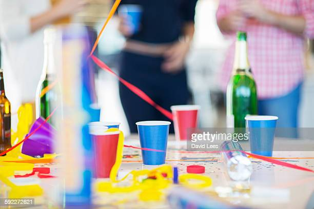 Champagne bottle and cups on table at office party