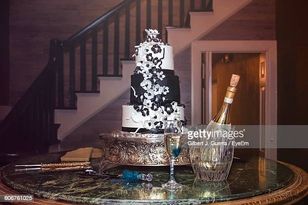Champagne Bottle And Flute By Cake On Table At Home