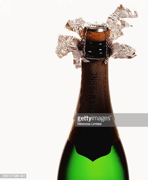 champagne bottle, foil unwrapped to reveal cork - microzoa stock pictures, royalty-free photos & images