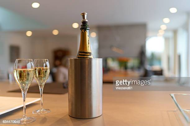 Champagne bottle in a cooler and two glasses of Champagne