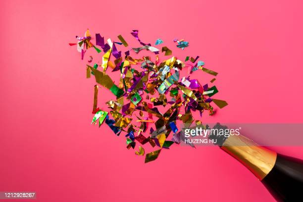 champagne bottle with confetti on pink background.  flat lay. - anniversary stock pictures, royalty-free photos & images