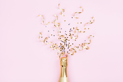 Champagne bottle with confetti stars and party streamers on pink background. Christmas, birthday or wedding concept. Flat lay. 1057557292