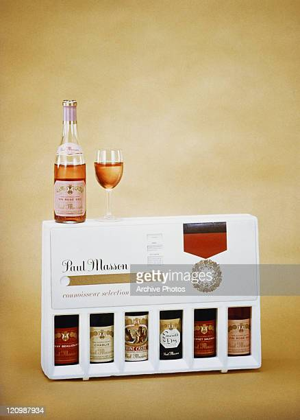 Champagne bottle with glass on champagne box against yellow background