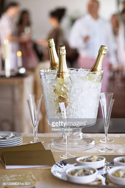 champagne bottles in ice bucket with glasses, people in background. - incidental people stock pictures, royalty-free photos & images
