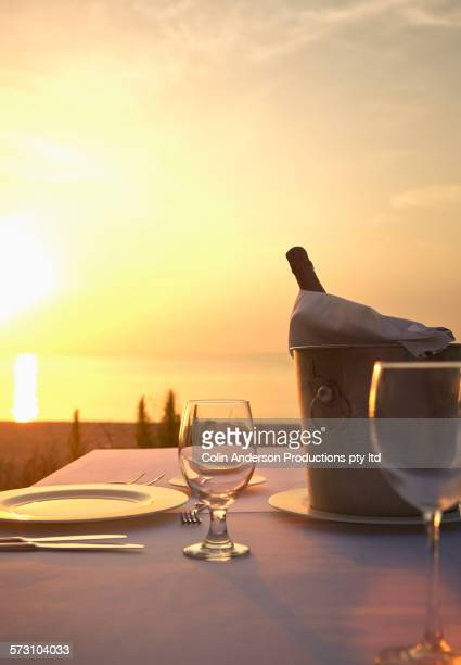 Champagne bucket at empty table at sunset