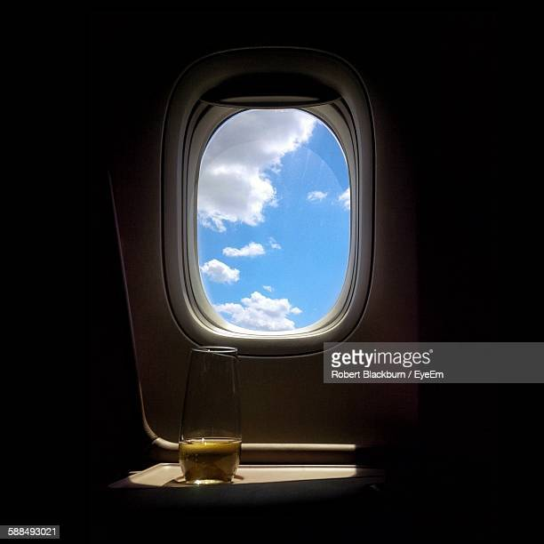 Champagne By Airplane Window Against Sky