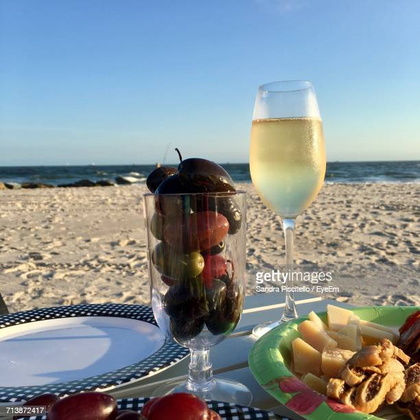 Champagne Flute With Cheese And Olives On Table At Beach During Sunny Day