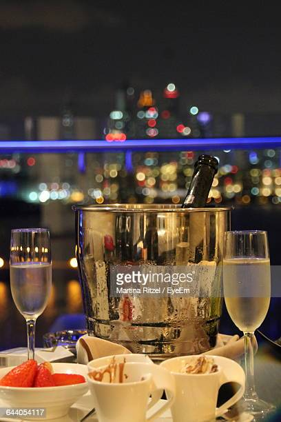 Champagne Flutes And Fruits On Restaurant Table At Night