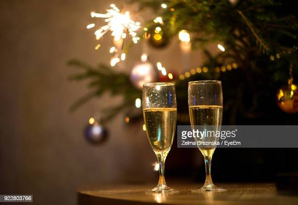 Champagne Flutes By Christmas Tree On Table
