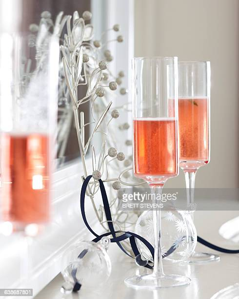Champagne flutes of pink champagne on mantelpiece with christmas decorations