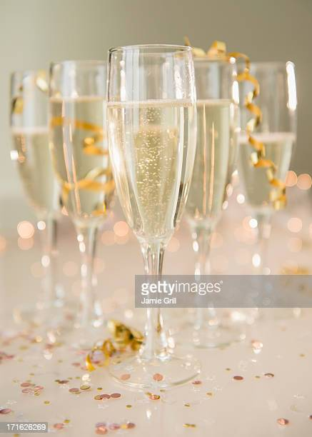 Champagne flutes on table decorated with confetti and streamer