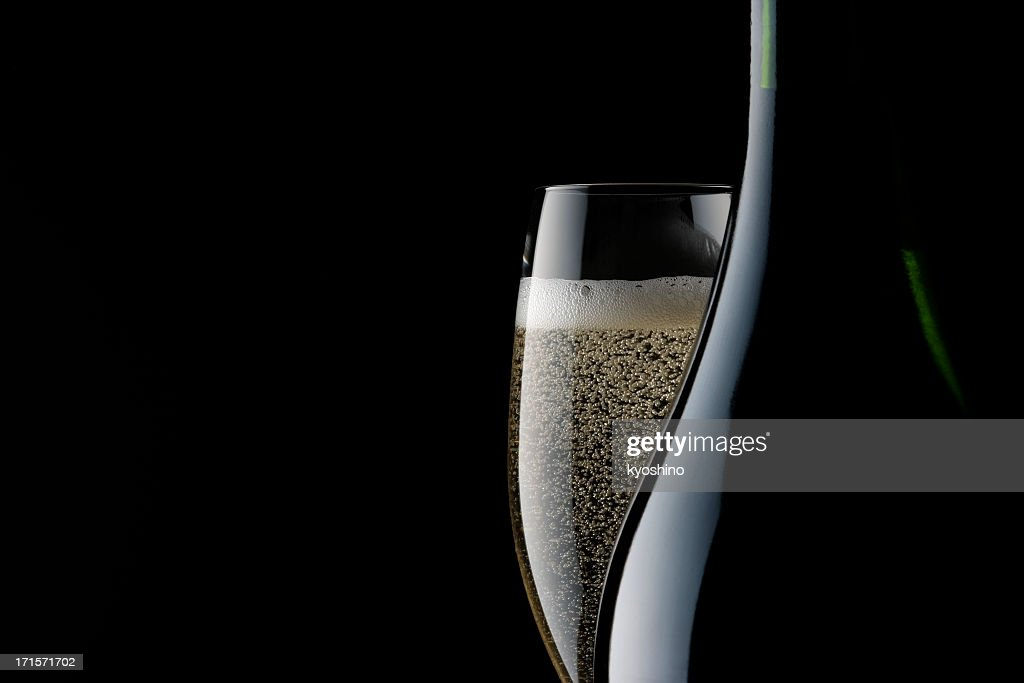 Champagne glass and blank bottle against black background : Stock Photo