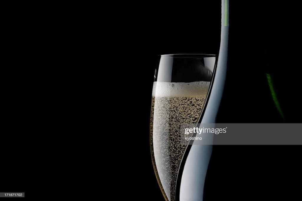 Champagner, Glas und leere Flasche vor schwarzem Hintergrund : Stock-Foto