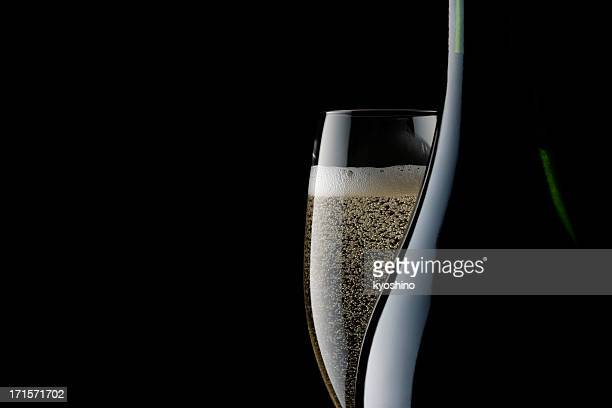 champagne glass and blank bottle against black background - bubble stock photos and pictures