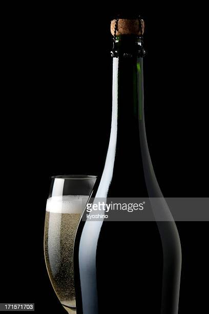 Champagne glass and blank bottle against black background