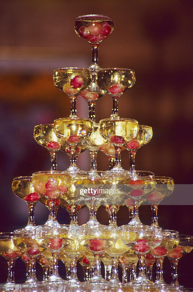 Champagne glass pyramid, glasses containing champagne and grapes : Stock Photo