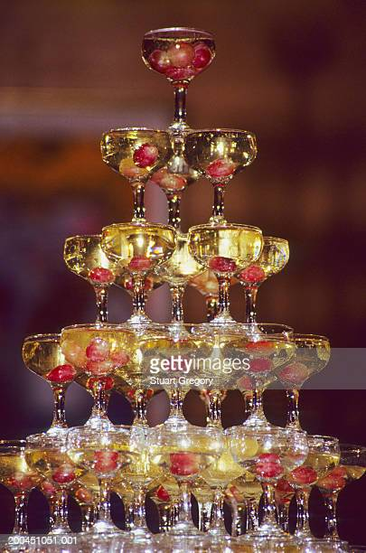 Champagne glass pyramid, glasses containing champagne and grapes
