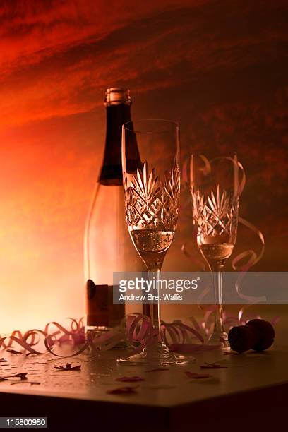 Champagne glasses & empty bottle outdside at dawn