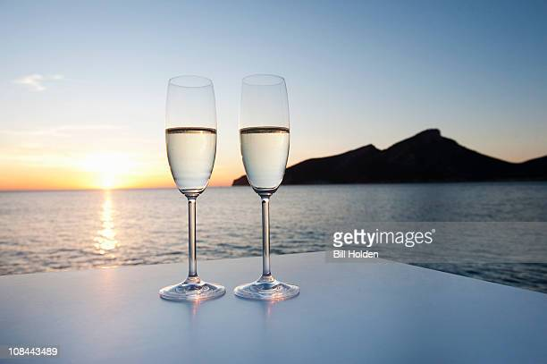 Champagne glasses shot against a sunset