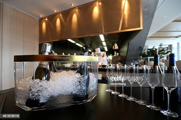 Champagne glasses stand near an ice bucket containing bottles of Louis Roederer champagne on the bar at the InterContinental Hotel Davos operated by...
