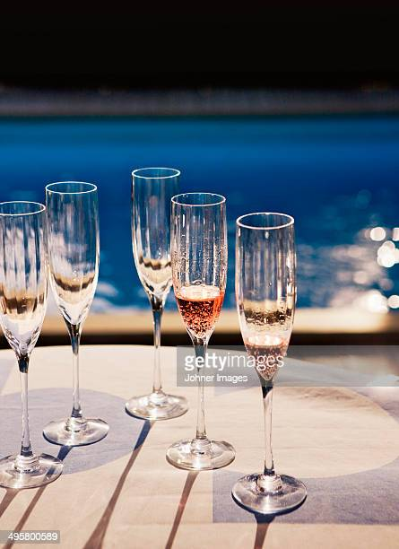 Champagne glasses, swimming pool in background