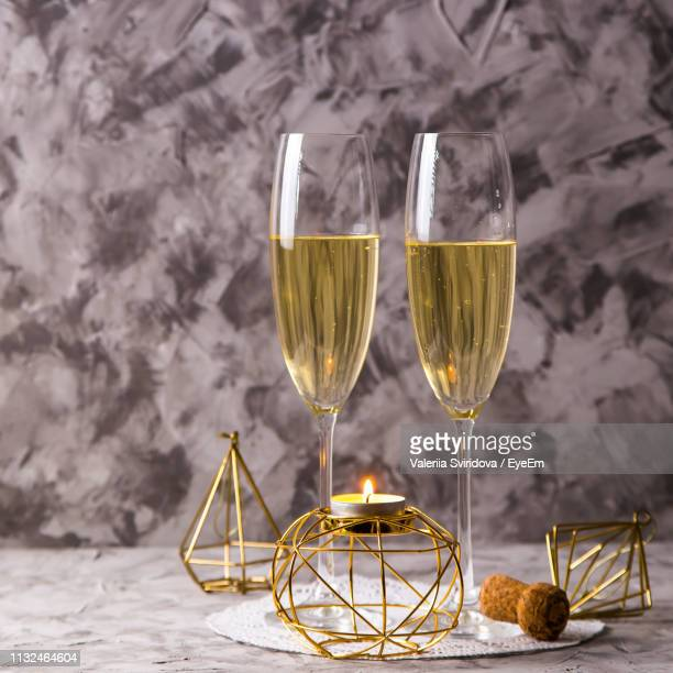 champagne in flutes with illuminated tea light candle on table - champagne flute stock pictures, royalty-free photos & images