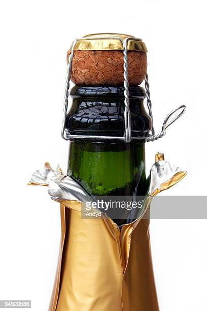 champagne in golden wrapper with cork and wire - champagne cork stock photos and pictures
