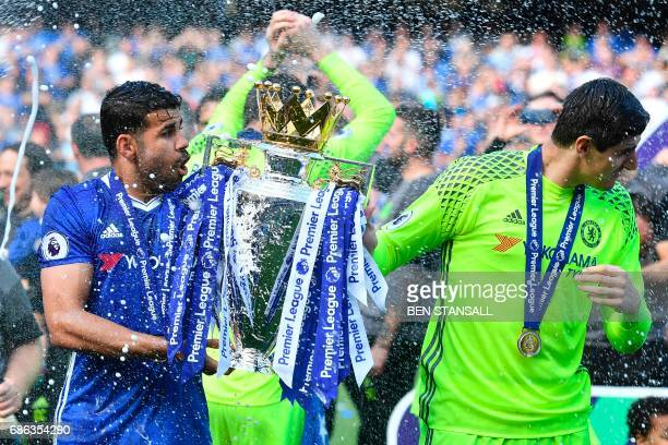 Champagne is sprayed at Chelsea's Brazilianborn Spanish striker Diego Costa and Chelsea's Belgian goalkeeper Thibaut Courtois as they hold the...