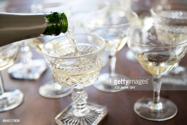 Champagne pouring from bottle into coupe