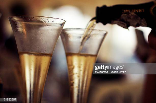 champagne pouring in glass - s0ulsurfing stock-fotos und bilder