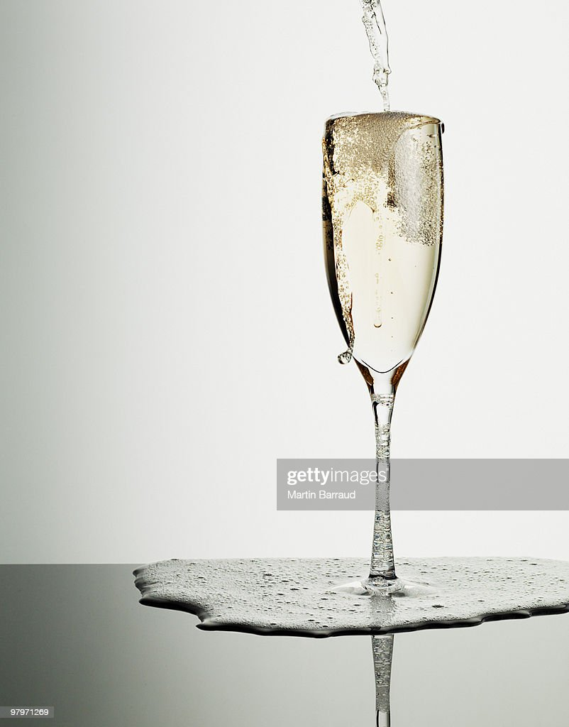 Champagne pouring into glass and overflowing : Stock Photo
