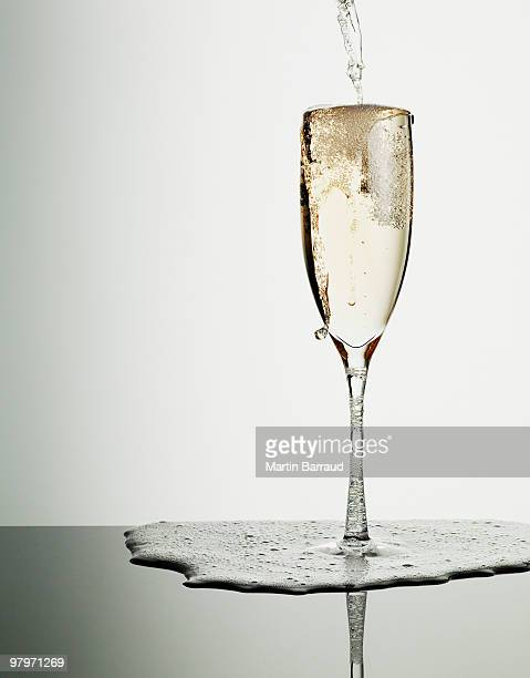 Champagne pouring into glass and overflowing