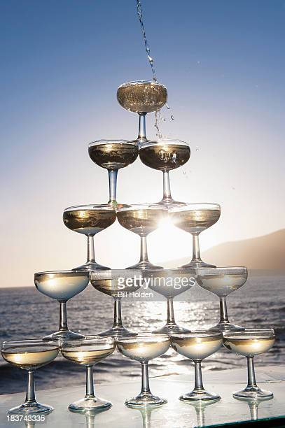 Champagne pouring into glasses with sea in background