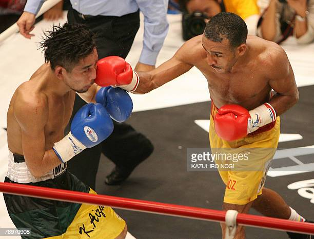 Champion Alexander Munos of Venezuela hits a right to Japanese challenger Kuniyuki Aizawa during the World Boxing Association super flyweight title...
