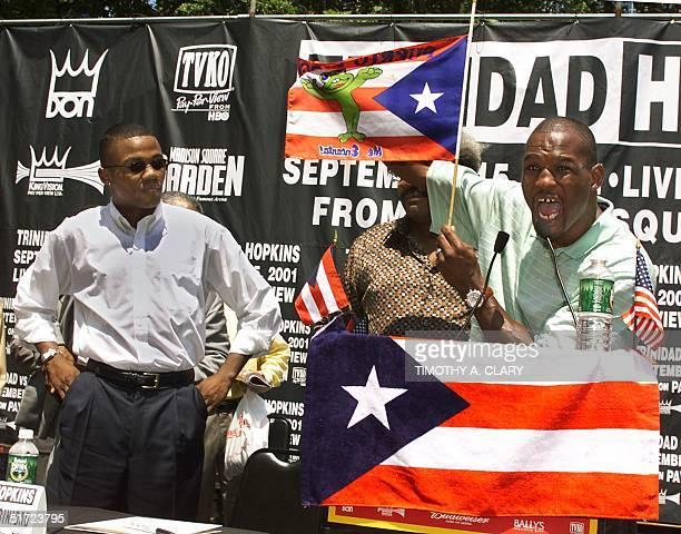 "Champion Felix ""Tito"" Trinidad of Puerto Rico looks on as IBF/WBC Champion Bernard ""The Executioner"" Hopkins of US holds up a flag at half mast..."