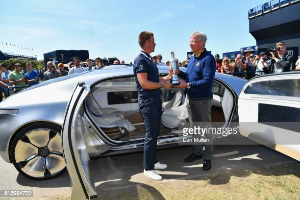 Champion Golfer of 2016 Henrik Stenson of Sweden returns the Claret Jug to RA Chief Executive Martin Slumbers during a practice round prior to the...