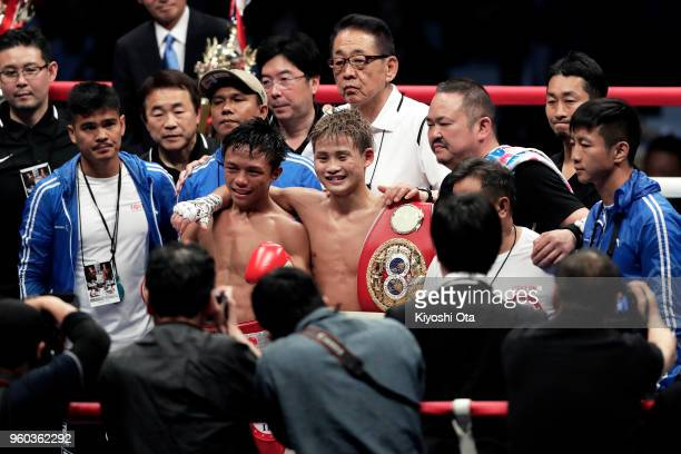 Champion Hiroto Kyoguchi of Japan celebrates as he poses for photographers with challenger Vince Paras of the Philippines after winning the IBF...