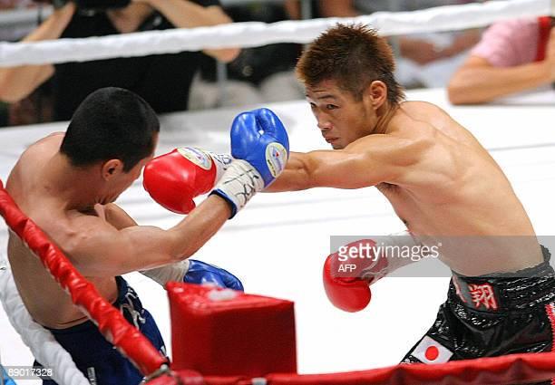 Champion Hozumi Hasegawa of Japan jabs challenger Nestor Rocha of the US in the first round of the WBC bantamweight title match in Kobe in Hyogo...