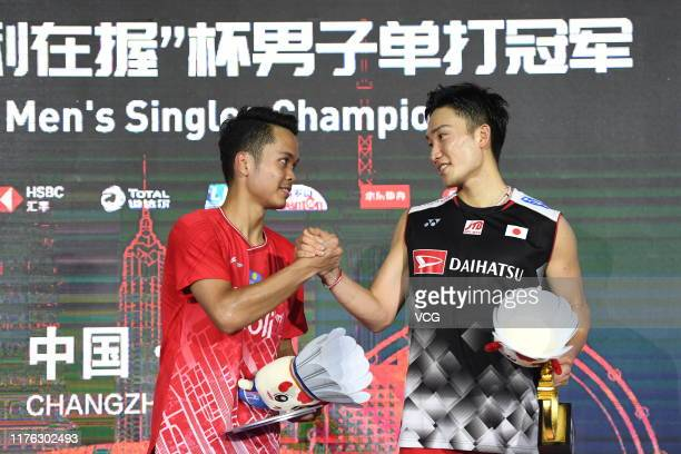 Champion Kento Momota of Japan shakes hands with the runner-up Anthony Sinisuka Ginting of Indonesia on the podium after the Men's Singles final...